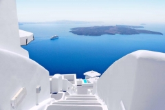 greece_santorini_white_concrete_staircases_leading_down_to_the_beautiful_bay_with_clear_blue_sky_and_sea_at_santorini